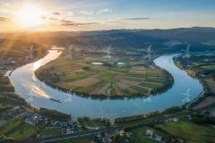 Donaubeuge bzw. Schlinge am Beginn des Nibelungengaus auf Höhe Ybbs-Persenbeug. (Luftaufnahme im frühsommerlichen Abendlicht) Im Hintergrund das Kraftwerk Ybbs-Persenbeug. Im Vordergrund die Westbahn.